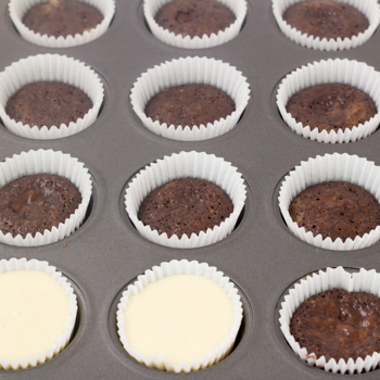 vanilla batter poured on top of chocolate batter in muffin tin ready to bake.