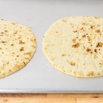 two pieces of plain naan bread