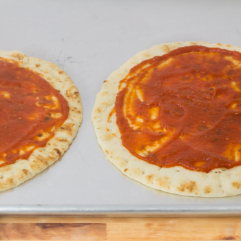 two pieces of naan with tomato sauce on top