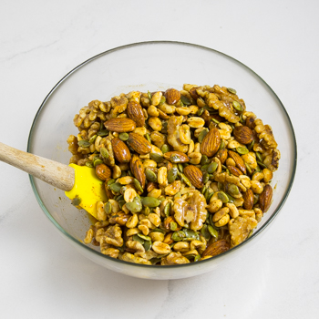 Glass mixing bowl full of mixed nuts with a small spatula