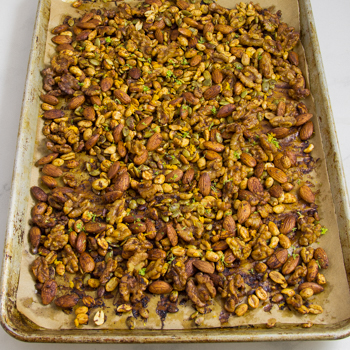 Parchment-lined baking sheet covered with a layer of roasted mixed nuts