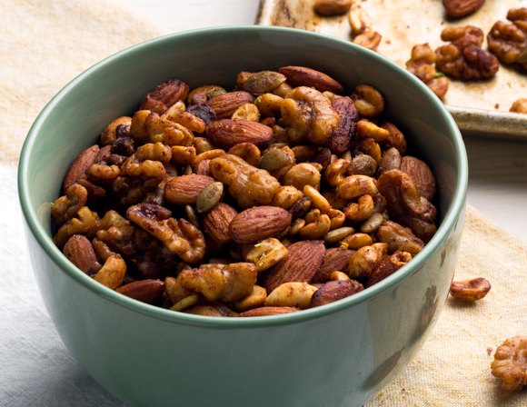 A bowl of roasted mixed nuts beside a baking sheet
