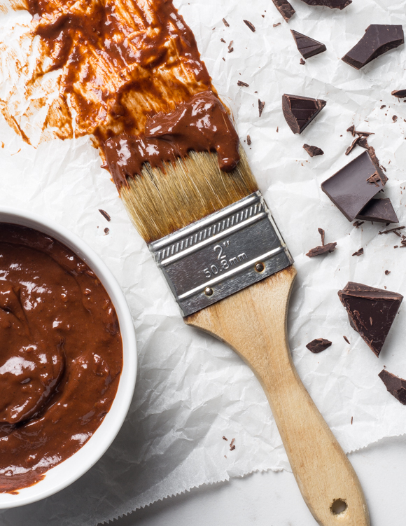 Paintbrush with barbecue sauce and broken pieces of chocolate