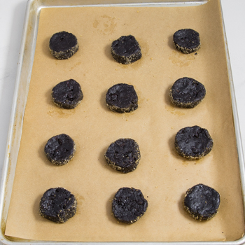 Unbaked dark chocolate cookies on a parchment-lined baking sheet