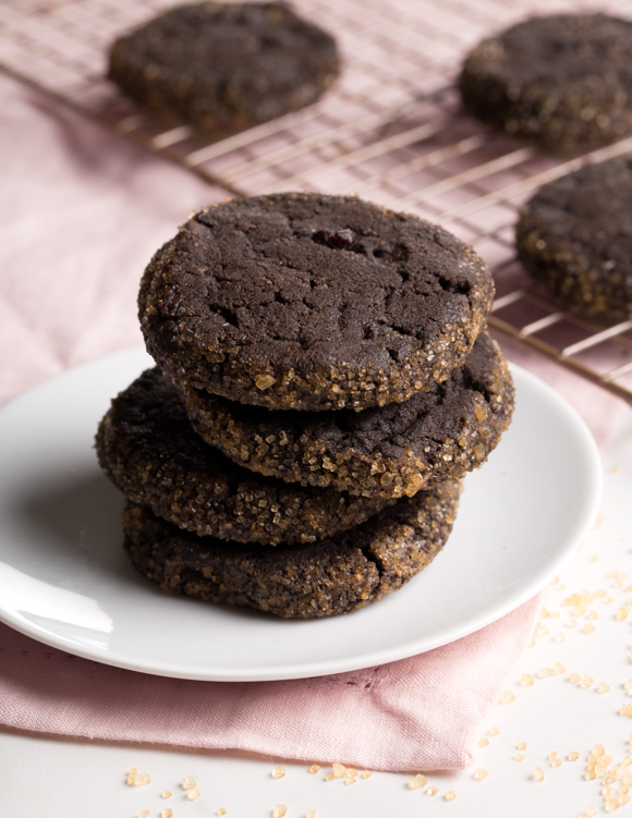 A stack of chocolate cookies with sugar-crusted sides on a white plate with more cookies on a wire cooling rack