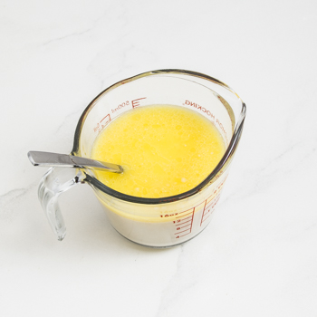 Glass measuring cup filled with melted margarine and egg yolk