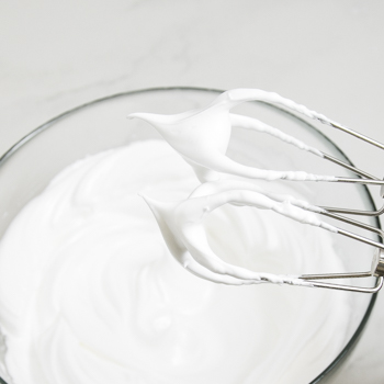 A glass mixing bowl of whipped egg whites, with stiff whites attached to the whisks