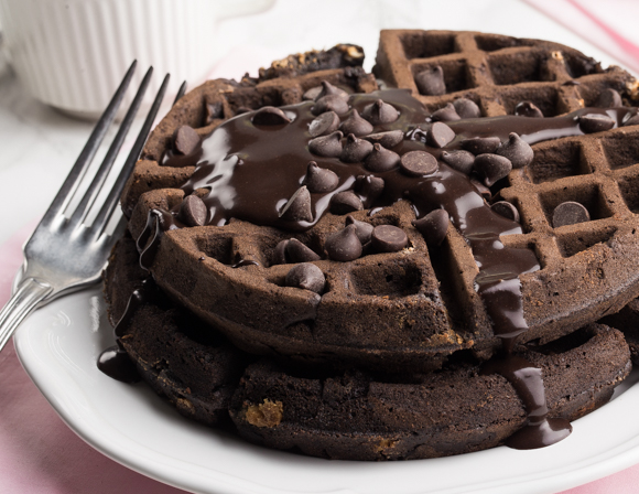 Two chocolate waffles with chocolate syrup and chocolate chips on a plate