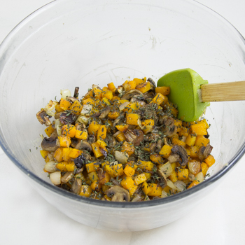 Cooked squash, onions and mushrooms in a mixing bowl with seasonings
