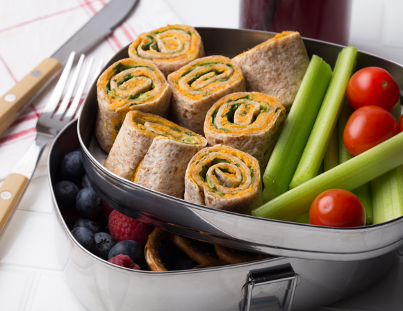 Hummus rolls in an open lunch container with vegetables and berries