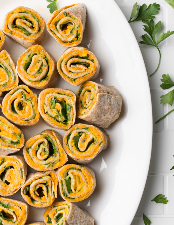 Sliced hummus rolls on a white platter garnished with parsley