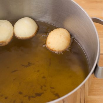 Beignets frying in a pot of oil.