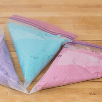 purple, blue, and pink food colouring in separate ziplock bags