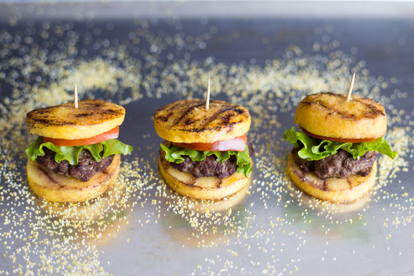 Grilled polenta used as burger buns with burgers finished on a platter.