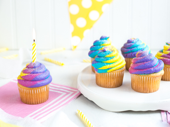 colour cupcakes with lit yellow birthday candle