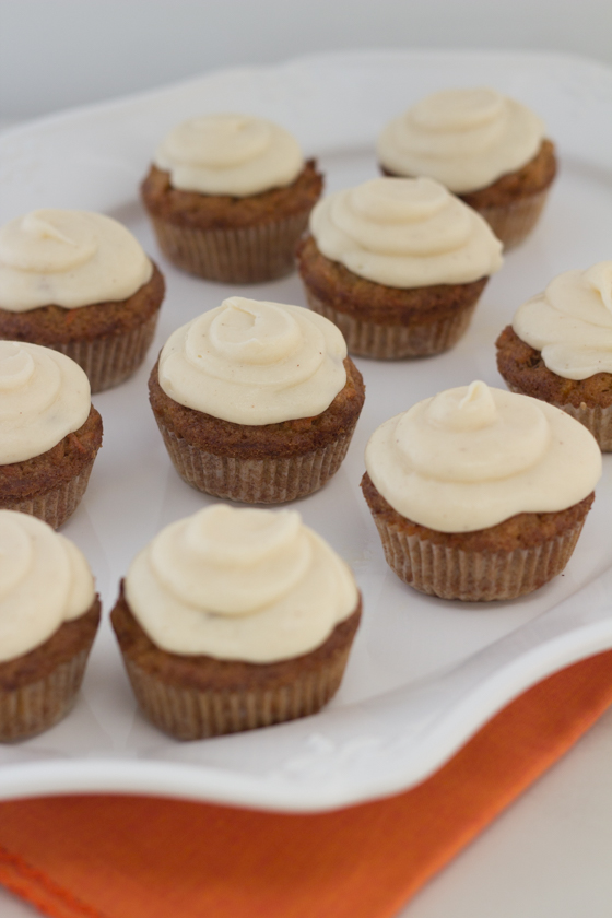 Carrot cake muffins with cream cheese frosting on plate.