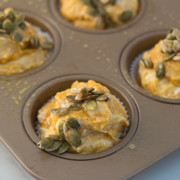 Raw muffin batter in a muffin mold sprinkled with pepita topping.