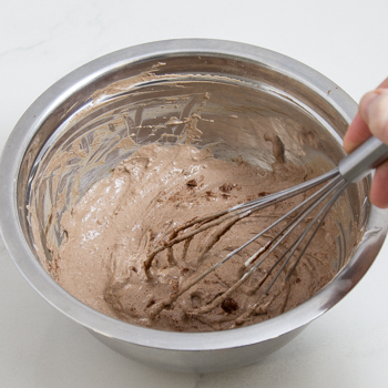 Metal mixing bowl with powdered ingredients being stirred into sour cream with a whisk