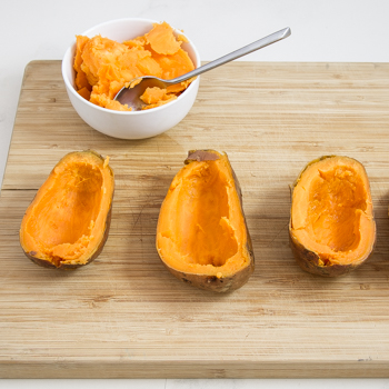 Three sweet potato halves with most of the flesh scooped out and a bowl of of sweet potato flesh