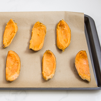 Sweet potatoes quartered lengthwise and sitting on a parchment-lined baking sheet