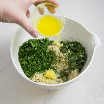 Pouring lemon juice into a mixing bowl of quinoa and minced vegetables