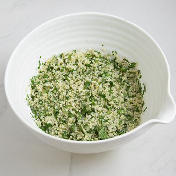 Mixing bowl of quinoa mixed with minced greens