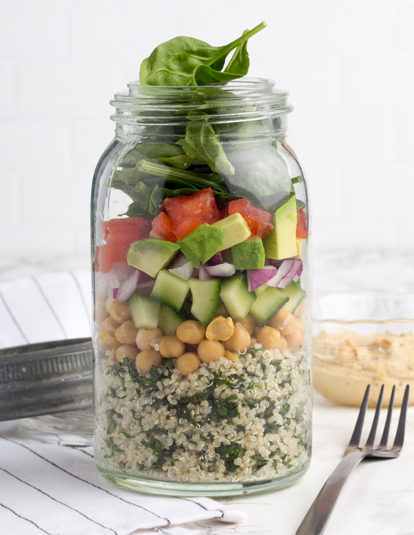 A jar of quinoa with chickpeas and vegetables, shown with a fork